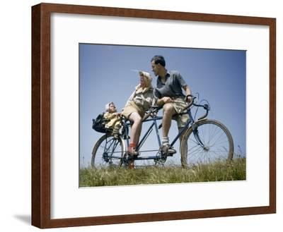 Man and Woman Straddling Tandem Bicycle Look at Child in Back Seat-B^ Anthony Stewart-Framed Photographic Print
