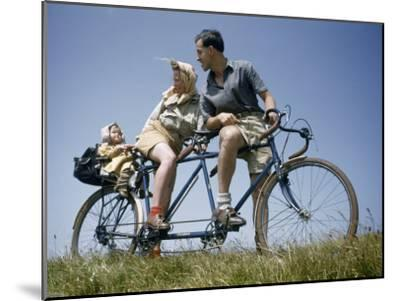Man and Woman Straddling Tandem Bicycle Look at Child in Back Seat-B^ Anthony Stewart-Mounted Photographic Print
