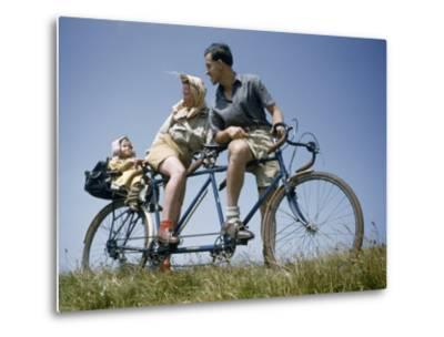 Man and Woman Straddling Tandem Bicycle Look at Child in Back Seat-B^ Anthony Stewart-Metal Print