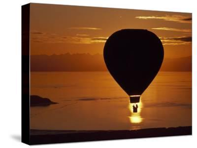 Riding in a Hot Air Balloon over Water at Sunset-Chris Johns-Stretched Canvas Print