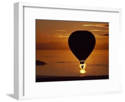 Riding in a Hot Air Balloon over Water at Sunset-Chris Johns-Framed Photographic Print