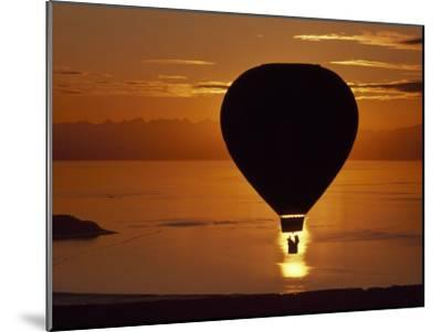 Riding in a Hot Air Balloon over Water at Sunset-Chris Johns-Mounted Photographic Print