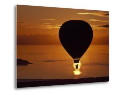 Riding in a Hot Air Balloon over Water at Sunset-Chris Johns-Metal Print