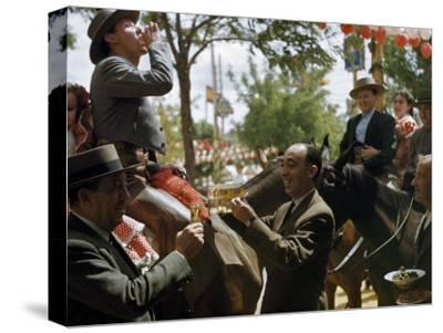 Man Offers Passing Friends a Glass of Wine-Luis Marden-Stretched Canvas Print