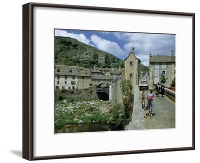 People in Riverside Village Walk across an Old Bridge-Walter Meayers Edwards-Framed Photographic Print