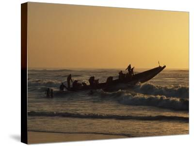Fishermen Launch their Boat into the Atlantic Ocean at Sunset-Amar Grover-Stretched Canvas Print