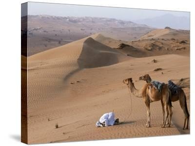 Kneeling to Pray in Desert, Holding Camels by Halters to Prevent Them Wandering Off Amongst Dunes-John Warburton-lee-Stretched Canvas Print