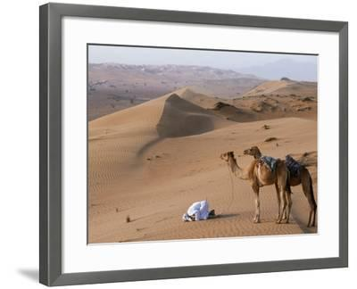 Kneeling to Pray in Desert, Holding Camels by Halters to Prevent Them Wandering Off Amongst Dunes-John Warburton-lee-Framed Photographic Print