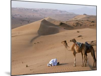Kneeling to Pray in Desert, Holding Camels by Halters to Prevent Them Wandering Off Amongst Dunes-John Warburton-lee-Mounted Photographic Print