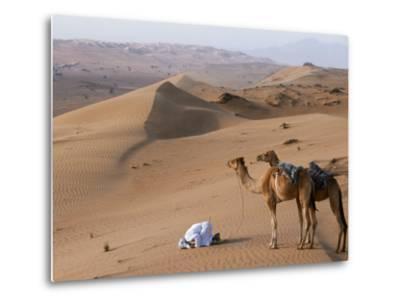 Kneeling to Pray in Desert, Holding Camels by Halters to Prevent Them Wandering Off Amongst Dunes-John Warburton-lee-Metal Print