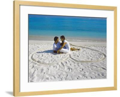 Young Couple on Beach Sitting in a Heart Shaped Imprint on the Sand, Maldives, Indian Ocean, Asia-Sakis Papadopoulos-Framed Photographic Print