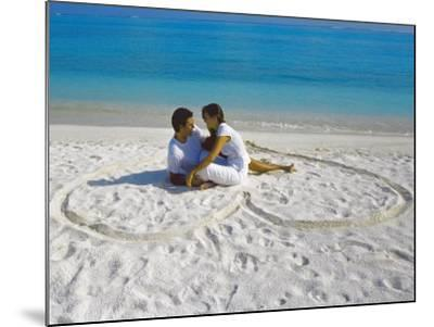 Young Couple on Beach Sitting in a Heart Shaped Imprint on the Sand, Maldives, Indian Ocean, Asia-Sakis Papadopoulos-Mounted Photographic Print