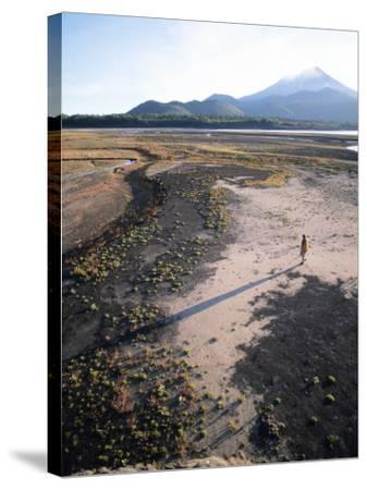 Man Walking on Dry Lake Bed with Llaima Volcano in Distance, Conguillio National Park, Chile-Aaron McCoy-Stretched Canvas Print