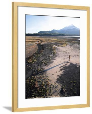 Man Walking on Dry Lake Bed with Llaima Volcano in Distance, Conguillio National Park, Chile-Aaron McCoy-Framed Photographic Print