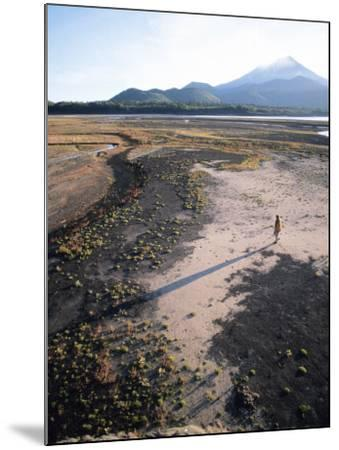 Man Walking on Dry Lake Bed with Llaima Volcano in Distance, Conguillio National Park, Chile-Aaron McCoy-Mounted Photographic Print