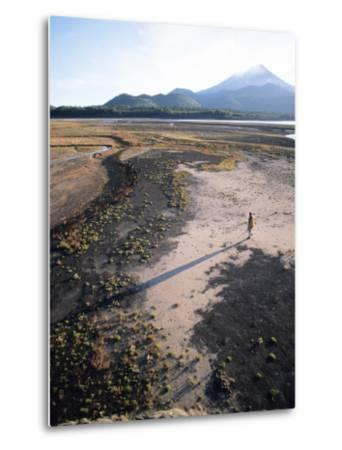 Man Walking on Dry Lake Bed with Llaima Volcano in Distance, Conguillio National Park, Chile-Aaron McCoy-Metal Print