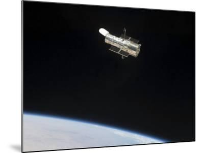 The Hubble Space Telescope in Orbit Above Earth--Mounted Photographic Print