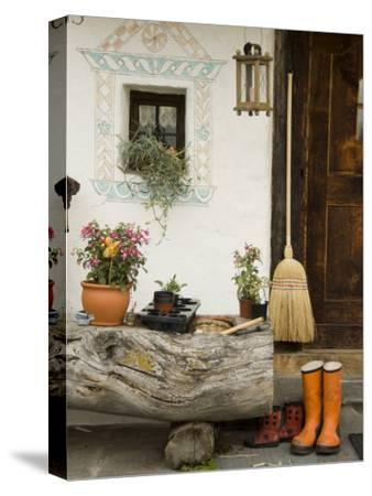 Boots, a Broom and Flowers Outside a Chalet-Annie Griffiths Belt-Stretched Canvas Print