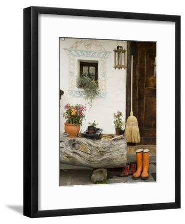 Boots, a Broom and Flowers Outside a Chalet-Annie Griffiths Belt-Framed Photographic Print