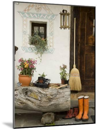 Boots, a Broom and Flowers Outside a Chalet-Annie Griffiths Belt-Mounted Photographic Print