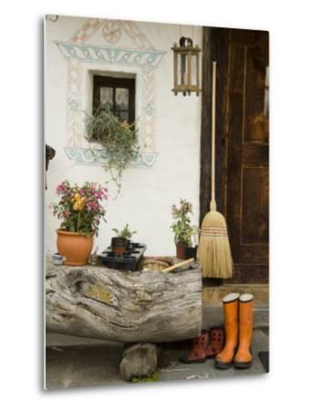 Boots, a Broom and Flowers Outside a Chalet-Annie Griffiths Belt-Metal Print