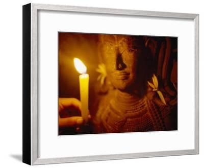 Man Holds a Candle Up to a Stone Carving at the Angkor Wat Temple-xPacifica-Framed Photographic Print