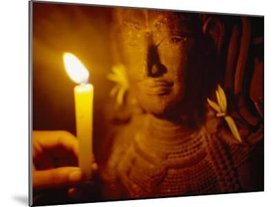 Man Holds a Candle Up to a Stone Carving at the Angkor Wat Temple-xPacifica-Mounted Photographic Print