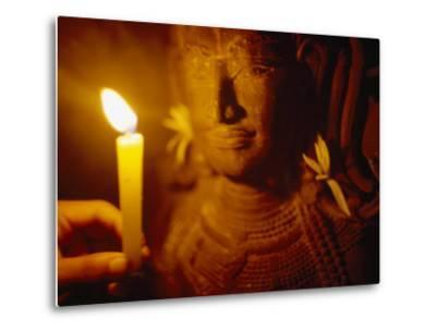 Man Holds a Candle Up to a Stone Carving at the Angkor Wat Temple-xPacifica-Metal Print