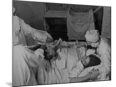 """Nurse at Her Head and Holding Her Hands, as She Gazes at Her Baby Boy after """"Painless"""" Childbirth-Alfred Eisenstaedt-Mounted Premium Photographic Print"""