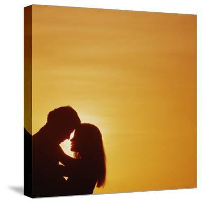 Silhouette of couple embracing at sunset-Dennis Hallinan-Stretched Canvas Print