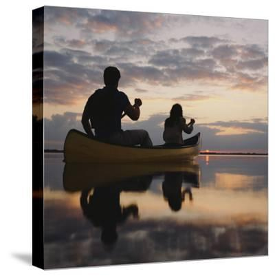 Couple Rowing Canoe in Lake at Sunset-Dennis Hallinan-Stretched Canvas Print
