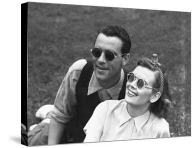 Couple Wearing Sunglasses Sitting on Grass, (B&W)-George Marks-Stretched Canvas Print