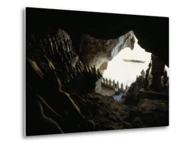 A Woman Kneels to Pray to Buddha in Sacred Cave High Above the Mekong-W^E^ Garrett-Metal Print