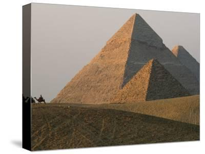 Camel Riders are Dwarfed by the Pyramids of Giza-James L^ Stanfield-Stretched Canvas Print