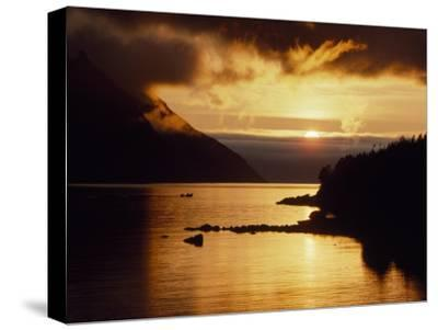Cloud-Filtered Sunset Silhouettes a Boat on the Sheltered Waters of Bonne Bay-Raymond Gehman-Stretched Canvas Print