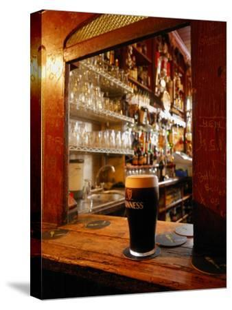 A Pint of Dark Beer Sits in a Pub Service Window-Jim Richardson-Stretched Canvas Print