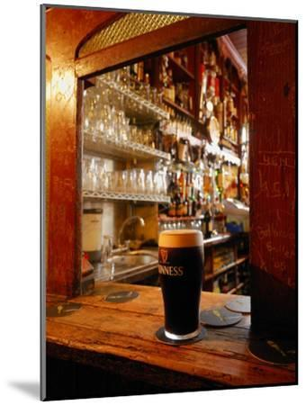 A Pint of Dark Beer Sits in a Pub Service Window-Jim Richardson-Mounted Photographic Print