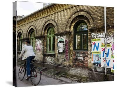 Cyclist in Freetown Christiania, with Anti European Union Posters on Wall-Christian Aslund-Stretched Canvas Print