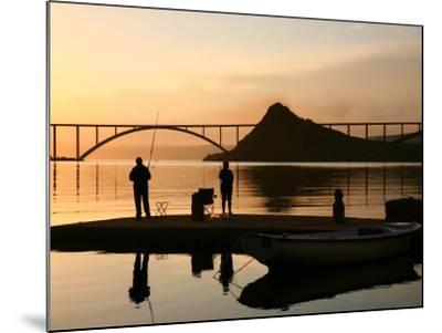 Couple Fishing from Stone Pier with Krk Bridge Joining Krk Island to Mainland-Ruth Eastham & Max Paoli-Mounted Photographic Print