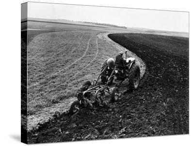 Man on Tractor Dragging Plough Through Vast Field, Rear View-H^ Armstrong Roberts-Stretched Canvas Print