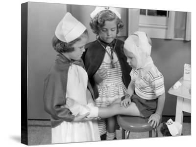 Two Young Girls Dressed As Nurses, Bandaging Three Year Old Boy's Head and Foot-H^ Armstrong Roberts-Stretched Canvas Print