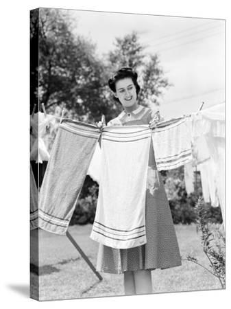 Woman Wearing a White Collar Poka Dot Cotton Dress While Pinning a Towel on a Clothes Line-H^ Armstrong Roberts-Stretched Canvas Print