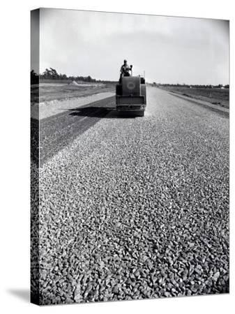 Highway Construction Worker Operating Heavy Machinery on Loose Gravel Road-H^ Armstrong Roberts-Stretched Canvas Print