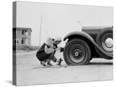 Woman Changing Flat Tire on Car-H^ Armstrong Roberts-Stretched Canvas Print