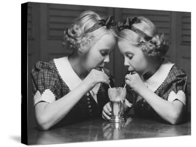 Twin Sisters Drinking Through Straws From Same Glass-George Marks-Stretched Canvas Print