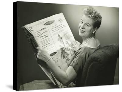 Woman Sitting in Armchair, Reading Newspaper, Smiling-George Marks-Stretched Canvas Print