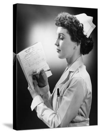 Young Nurse Writing on File in Studio-George Marks-Stretched Canvas Print