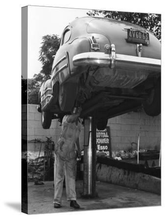 Mechanic Working on Underside of Car-George Marks-Stretched Canvas Print