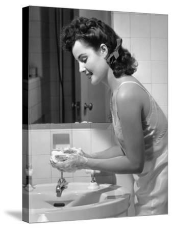 Woman Washing Hands at Bathroom Sink-George Marks-Stretched Canvas Print