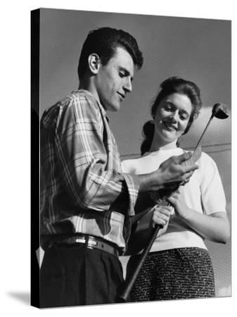 Man Showing Golf Club To Woman--Stretched Canvas Print